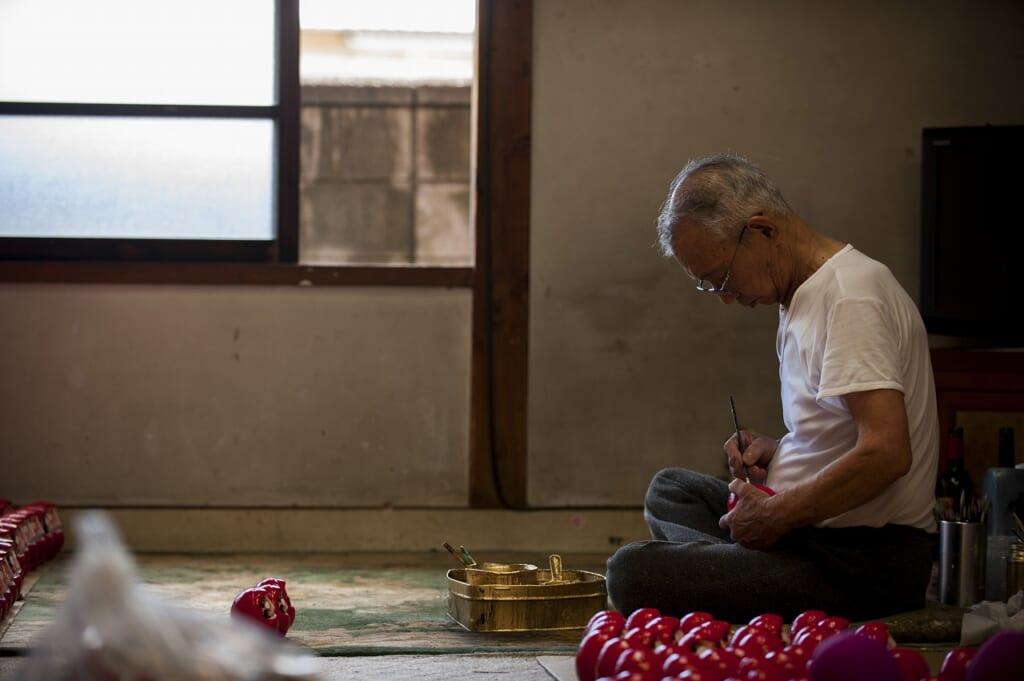 Pintando un daruma, uno de los productos japoneses incluidos