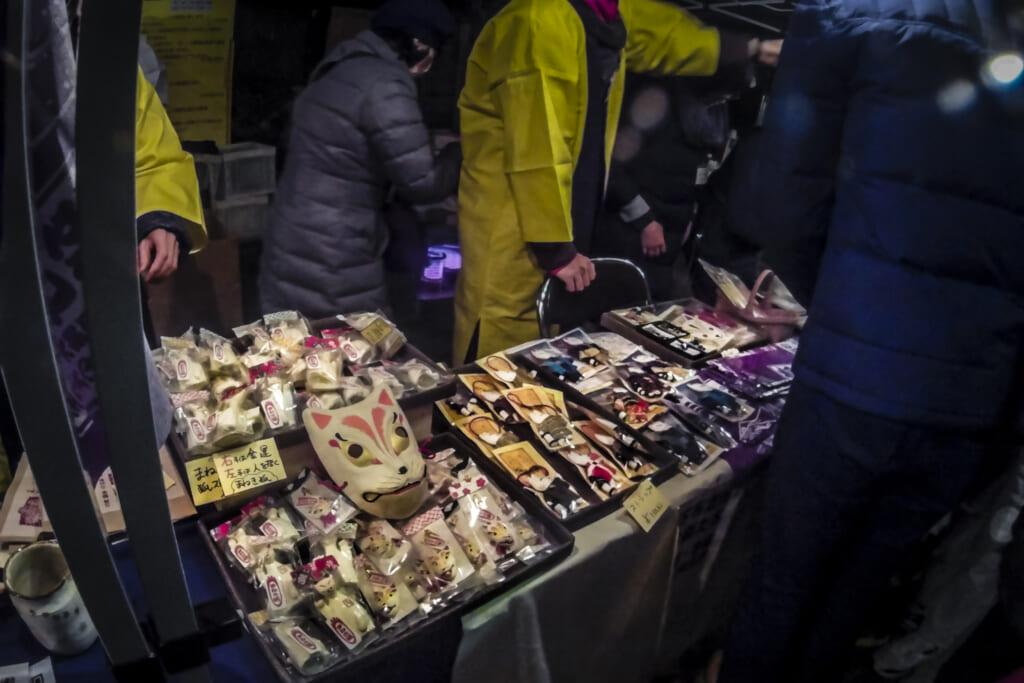 Puestos callejeros vendiendo máscaras y adornos de zorros durante el Kitsune no Gyoretsu