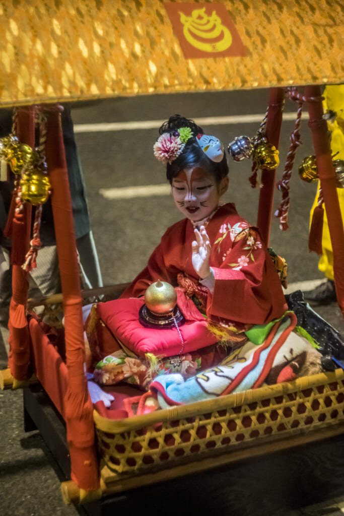 Una joven zorro a bordo de un pequeño palanquin durante el Kitsune no Gyoretsu
