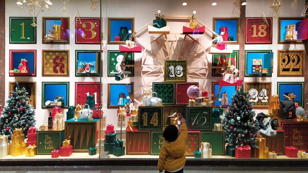 Un niño delante de un escaparate navideño en Japón
