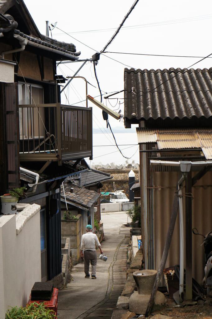 Anciano caminando por las calles de un pueblo portuario japonés
