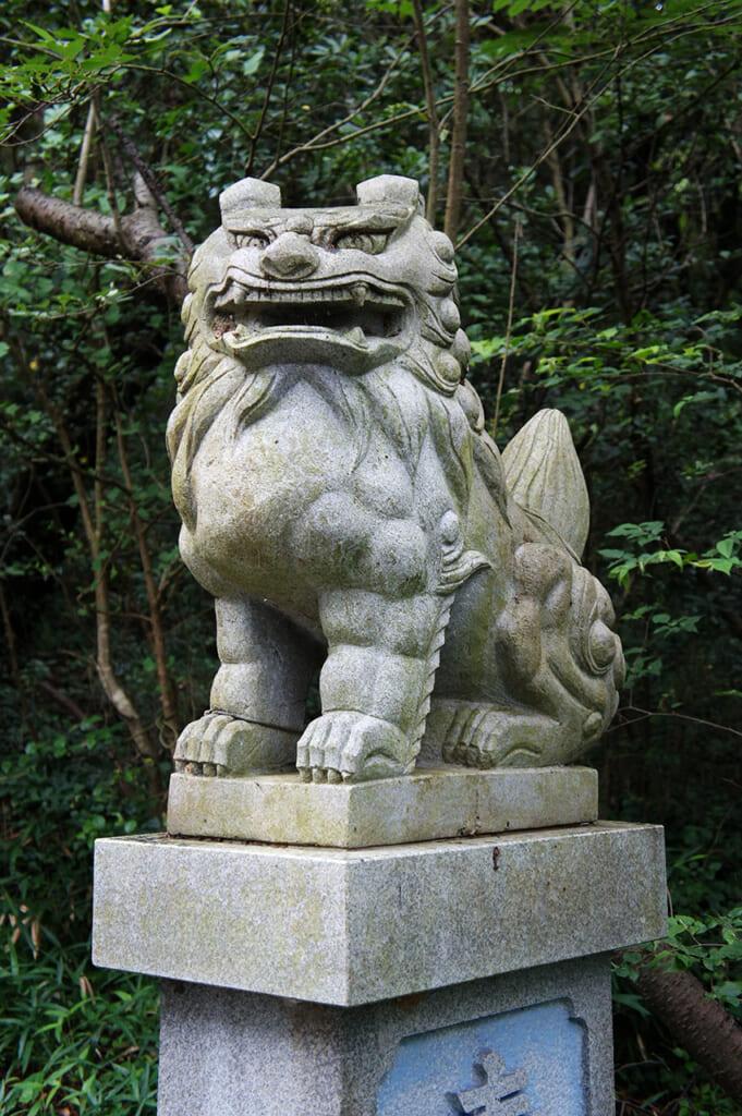 Un perro en la entrada del hachiman jinja en Manabeshima