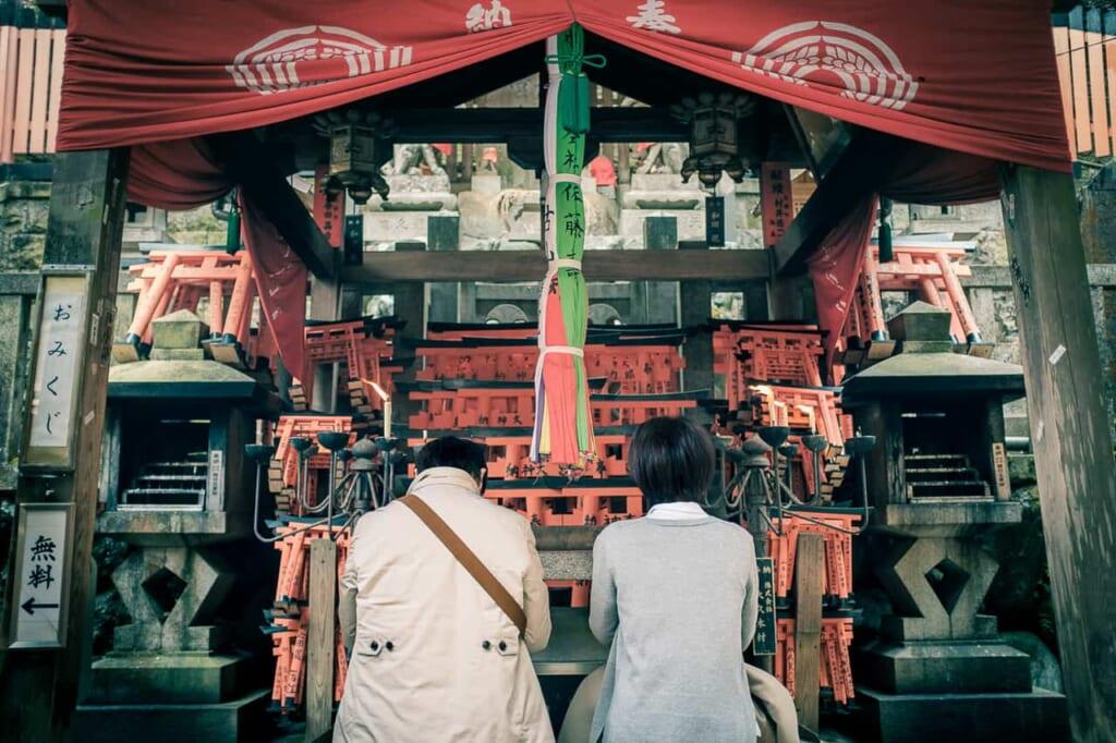 Dos personas rezando delante de un altar en Kioto