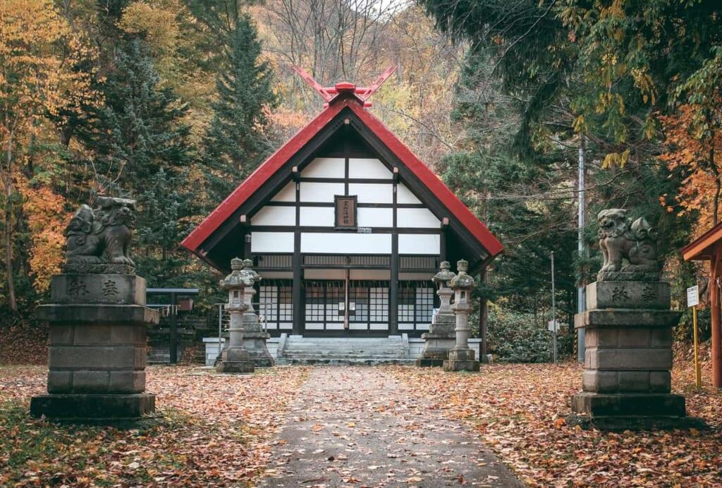 Un pequeño santuario japonés con dos koaminu custodiando