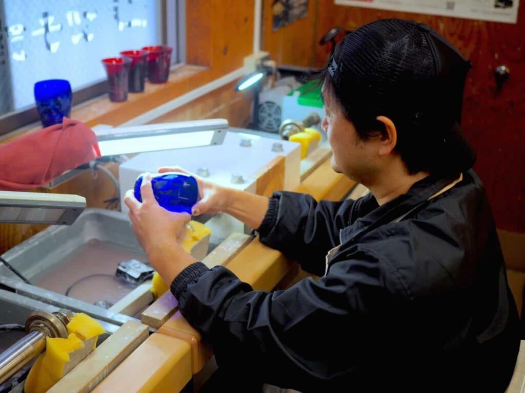 Un artesano mostrando cómo realizar los patrones en el vaso