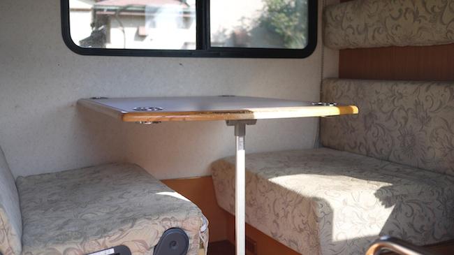 Una mesa con sus sofás dentro de la caravana
