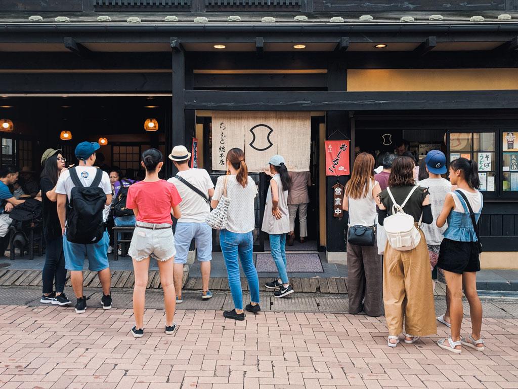 Touristen vor einem traditionellen japanischen Laden