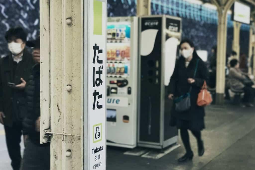 Japaner, die in der Öffentlichkeit Masken tragen.