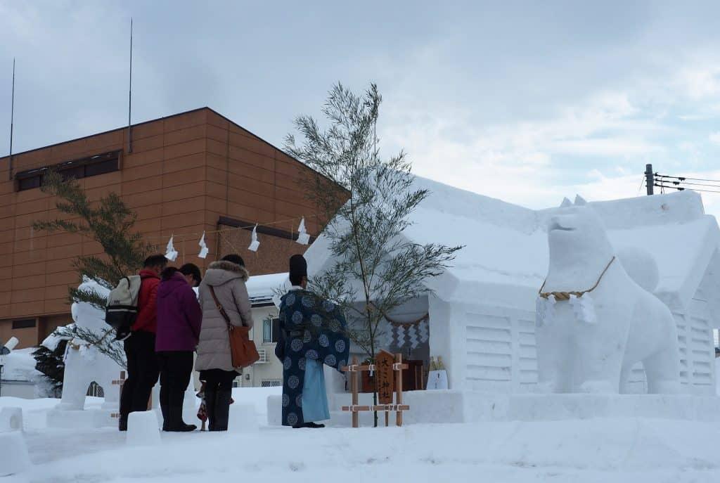Ein Schrein aus Schnee, der von zwei Schneehundeskulpturen bewacht wird.