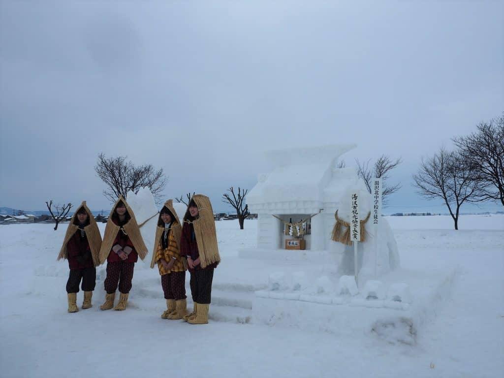 Mädchen vor einem Schrein aus Schnee.