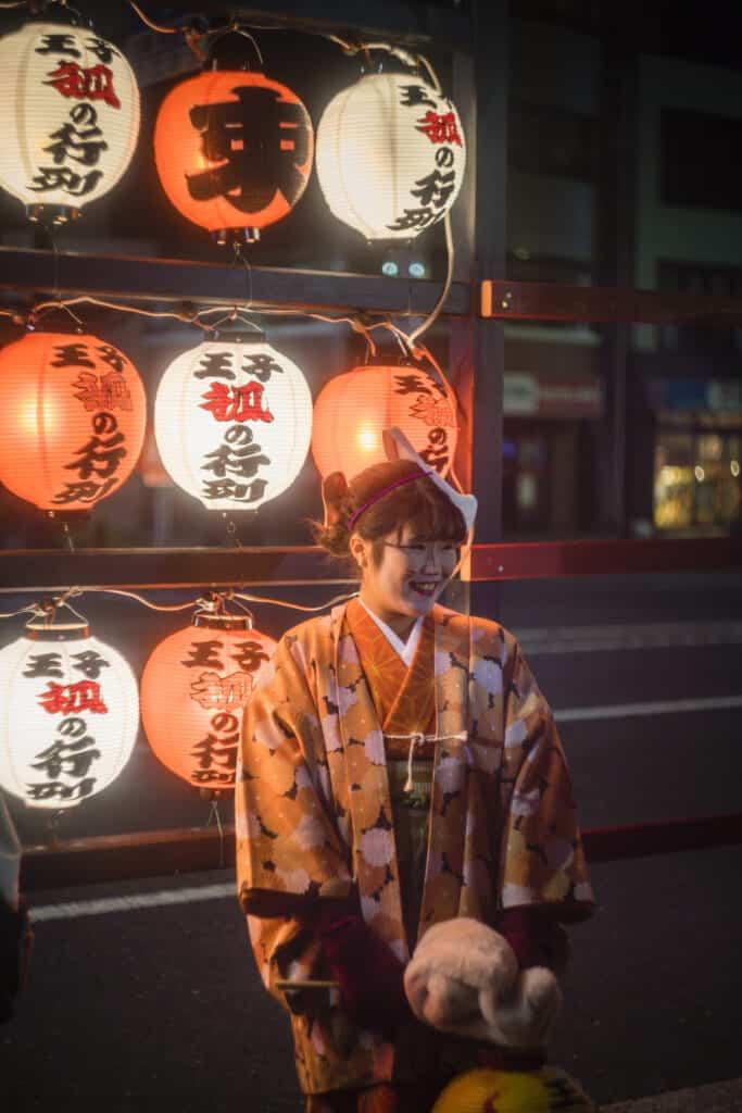 Mädchen im Kimono und Fuchsmaske auf dem Kitsune no Gyoretsu Fest in Oji.