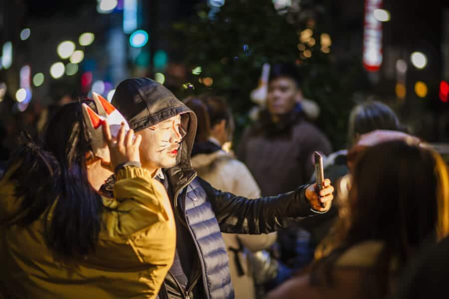 Besucher auf dem Kitsune no Gyoretsu Fest mit Fuchs-Make-up.