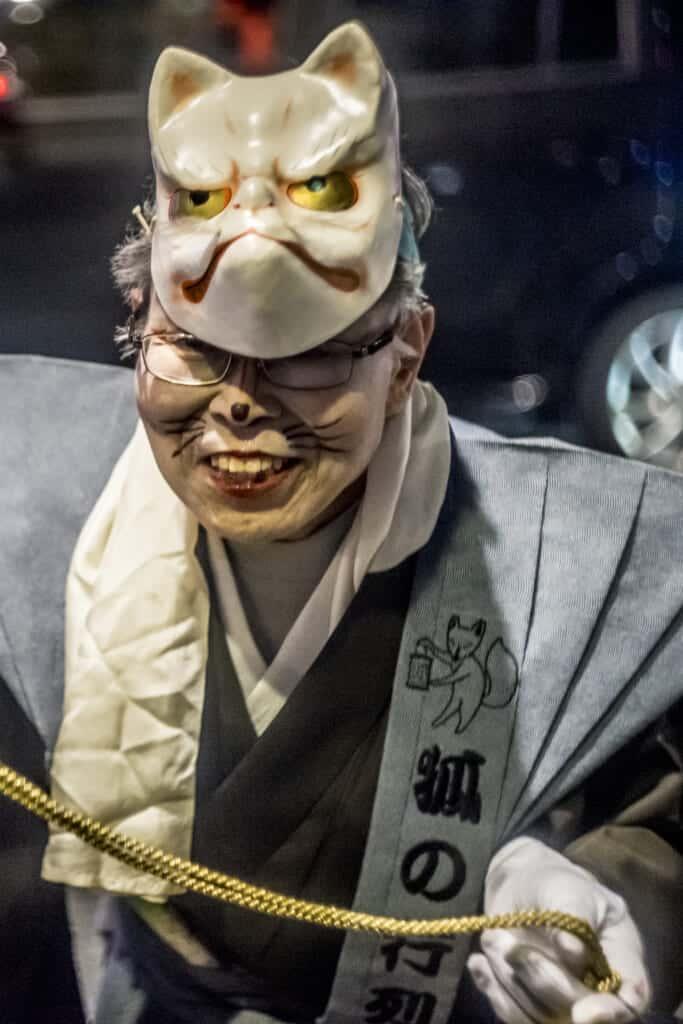 Eine Besucherin auf dem Kitsune no Gyoretsu Fest mit einer Fuchsmaske.