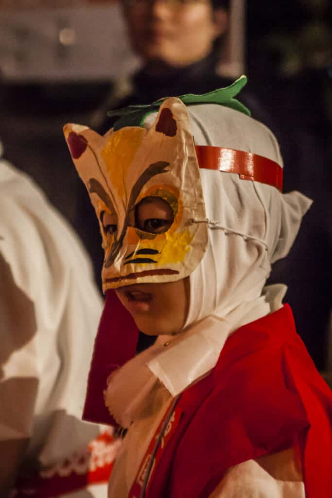 Ein Kind mit einer Fuchsmaske auf dem Kitsune no Gyoretsu Fest.