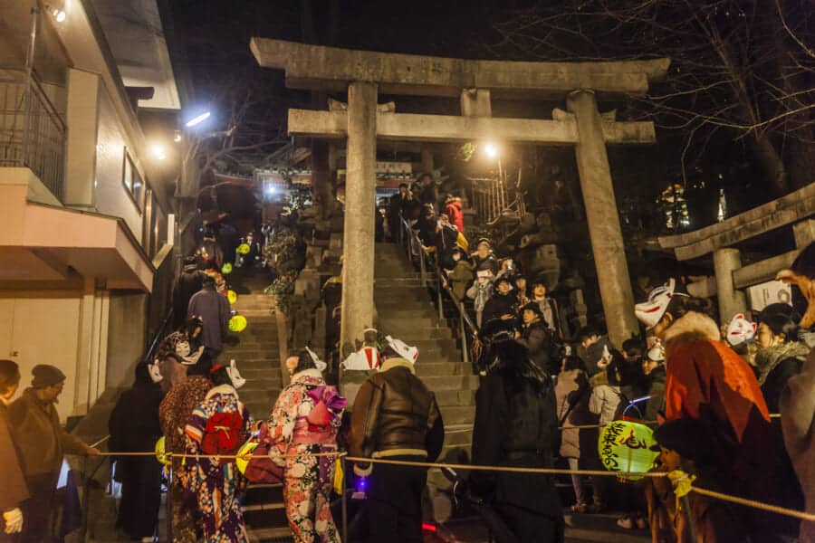 Die Teilnehmer gehen die Treppen am Oji Inari Jinja-Schrein rauf.
