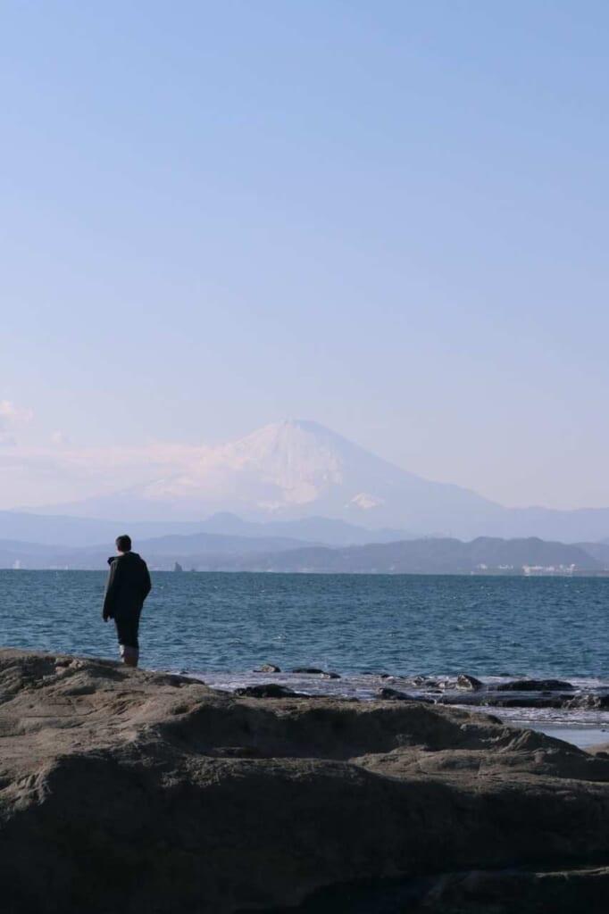 Uomo osserva il mare e il Monte Fuji dalla costa
