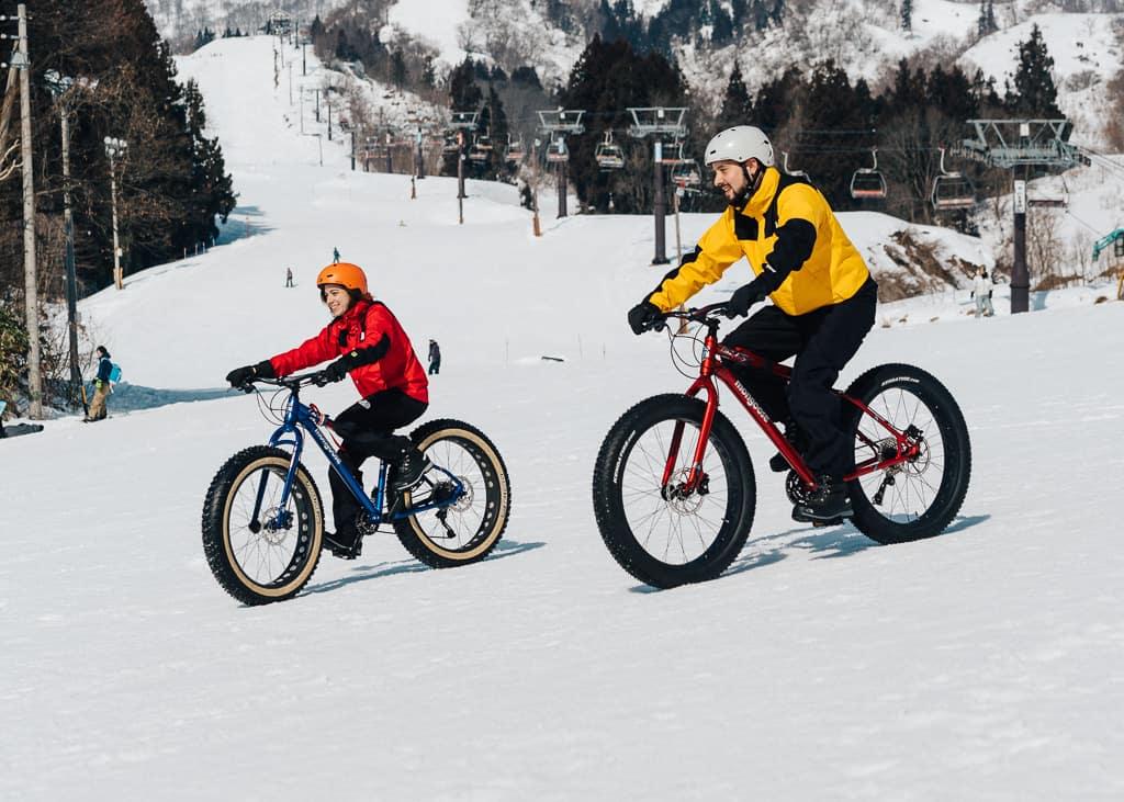 due biciclette downhill scendono da una montagna innevata