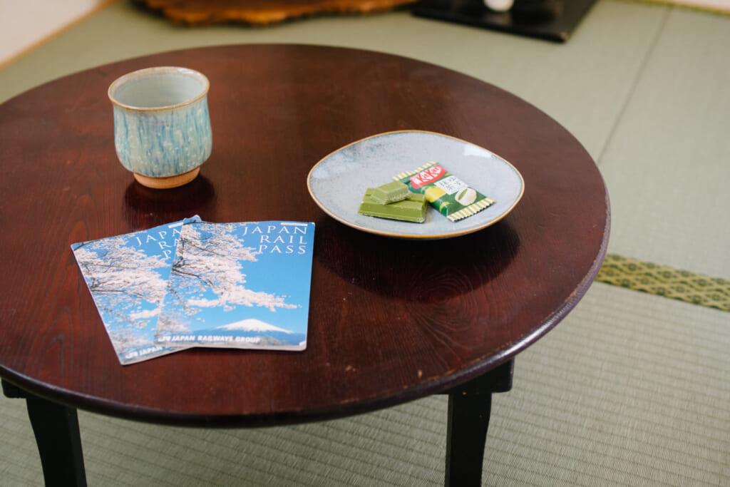 Due JR Pass su un tavolino giapponese con dolcetti e tazza di tè in una stanza con il tatami.