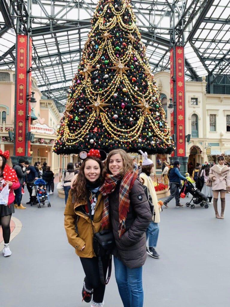 L'autrice Maria e un'amica davanti all'albero di Natale a Disneyland