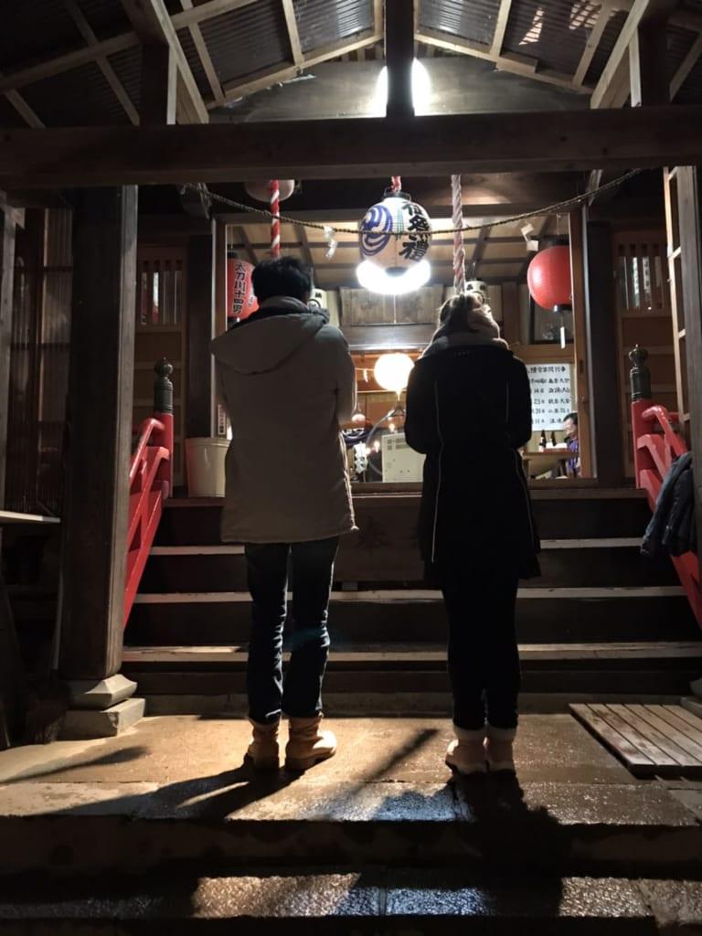 Due persone pregano al tempio shintoista la notte di capodanno