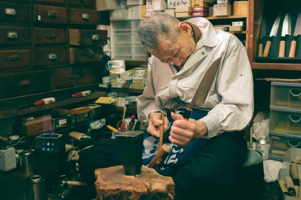 Artigiano che monta un manico e una lama, negozio Wada, Sakai, Osaka, Giappone