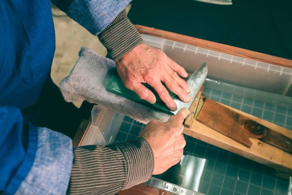 Dettaglio di Artigiano che ripara una lama su una pietra ad acqua, negozio Wada, Sakai, Osaka, Giappone
