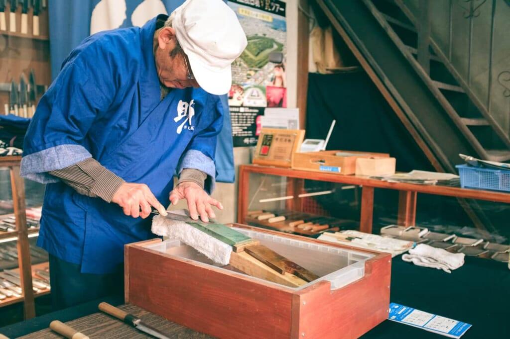Artigiano che ripara una lama su una pietra ad acqua, negozio Wada, Sakai, Osaka, Giappone