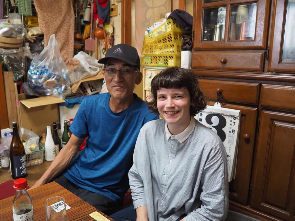 Una ragazza occidentale e un uomo giapponese sono seduti un tavolo uno affianco all'altra