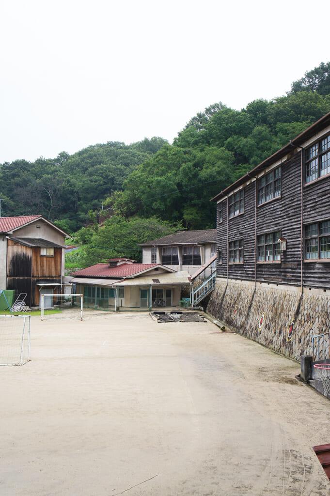Un piazzale circondato da vecchie case con un piccolo campo da calcio