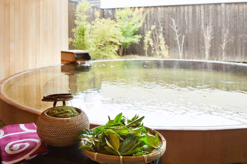 Vasca termale con foglie di tè verde immerse nell'acqua