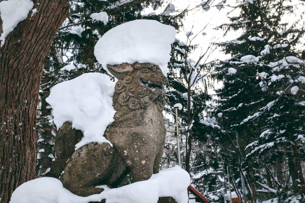 Una statua komainu coperta di neve
