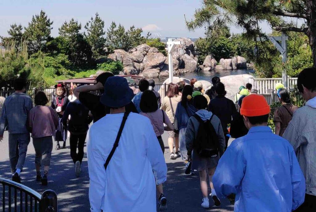 Persone in fila a Tokyo DisneySea con monte Fuji sullo sfondo